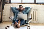 istock Serene barefoot guy resting, daydreaming at home. 1199863539