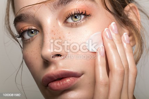 Closeup studio shot of a beautiful young woman with freckles skin, applying moisturiser to her face. Posing against a grey background