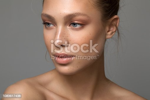 Closeup studio shot of a beautiful young woman with freckles skin posing against a grey background