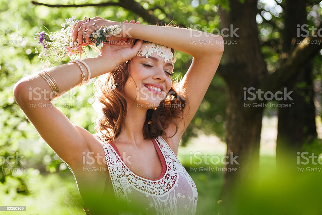 Serene boho girl looking relaxed in a summer park stock photo