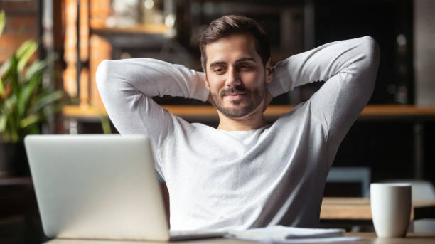 Serene businessman sitting at table feels satisfied accomplishing work Caucasian businessman sitting at table in cafe modern cozy office looking at laptop screen feels satisfied proud with done work, serene man resting putting hands behind head relaxing no stress concept smooth stock pictures, royalty-free photos & images