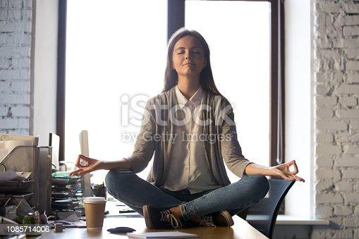 istock Serene calm business woman sit on office desk meditating 1085714006