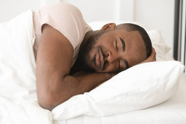 Serene calm young black man sleeping well alone in bed Serene calm handsome young black man sleeping well alone on orthopedic soft pillow under warm duvet, african american guy lying asleep in comfortable cozy bed enjoy good night peaceful healthy sleep sleeping stock pictures, royalty-free photos & images