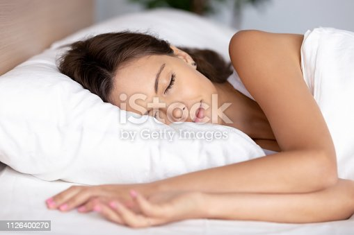 istock Serene calm young woman sleeping well on orthopedic soft pillow 1126400270