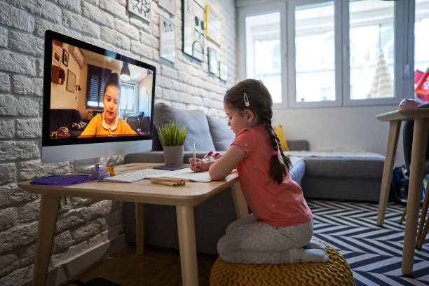 Serene children drawing together over a video call during a covid-19 outbreak stock photo