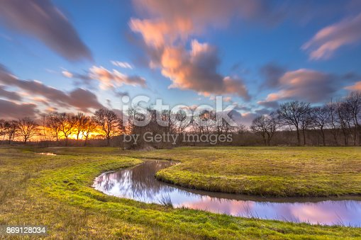 istock Serene Creek with Blurred Clouds 869128034