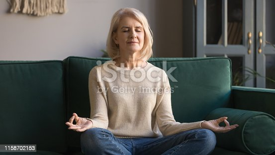 istock Serene elderly woman sit in lotus position meditating at home 1158702153