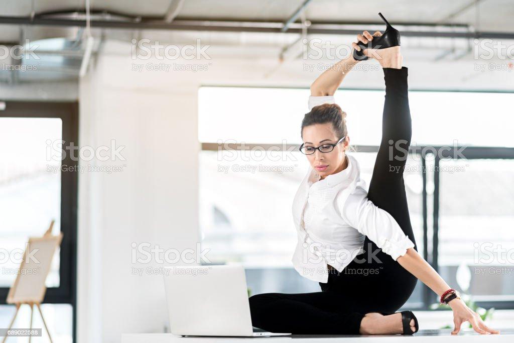 Serene female making gymnastic exercise during job stock photo