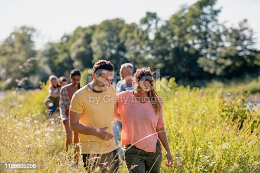 Couple walking through a field with their arms around each other. Their friends are walking behind them.