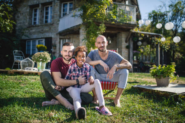 Serene gay family with a adopted daughter stock photo