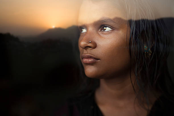 Serene girl looking at sunset view from behind glass window. stock photo