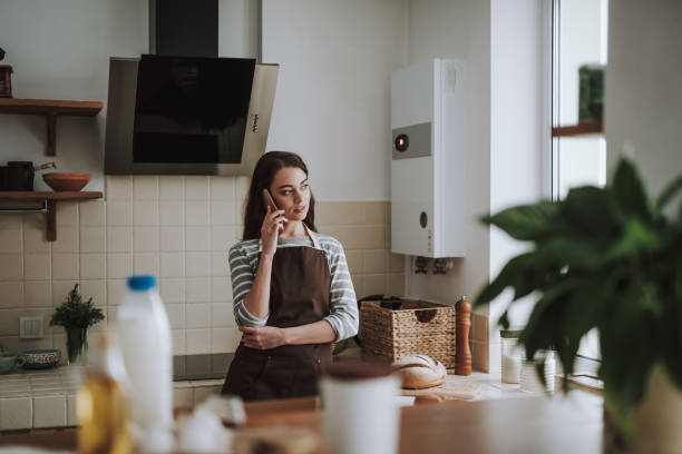 Serene lady is speaking on phone in kitchen stock photo