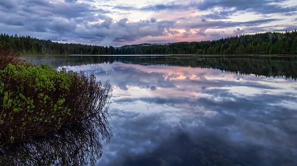 Serene lake reflection with purple sky stock photo