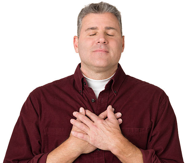 Serene Mature Man With Hands On Chest stock photo