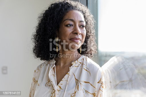 The serene mature woman daydreams while looking out the window of her office.
