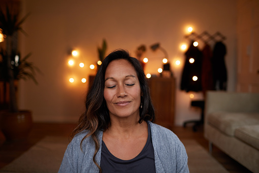 Serene woman smiling with her eyes closed while sitting on her living room floor practicing yoga