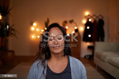 istock Serene mature woman smiling while meditating at home 1197853111