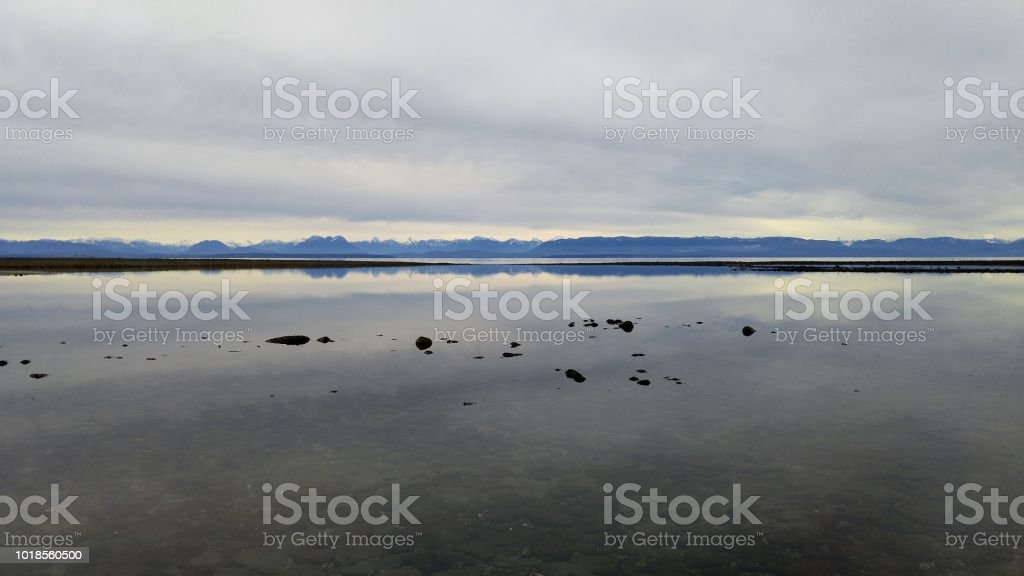 A serene seascape and view of mountains as the tide rolls out in spring stock photo