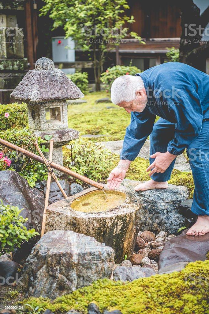 Serene Senior Caucasian Man in Buddhist Temple Garden, Kyoto, Japan royalty-free stock photo