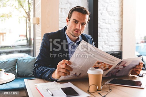 Serious stubbled businessman looking at newspaper while locating at desk in room
