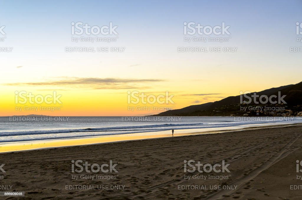 Serene sunset sky on the beach with silhouette of lone runner stock photo