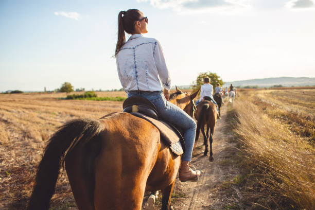 Serene tourist woman riding a horse with a tourist group stock photo