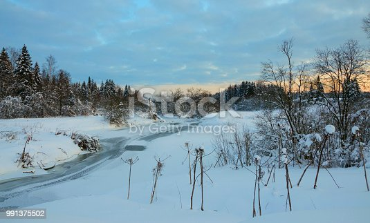 1034754000istockphoto Serene winter landscape with snow covered trees and ice-bound river. 991375502