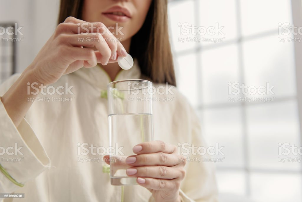 Serene woman adding vitamin liquid - foto de stock