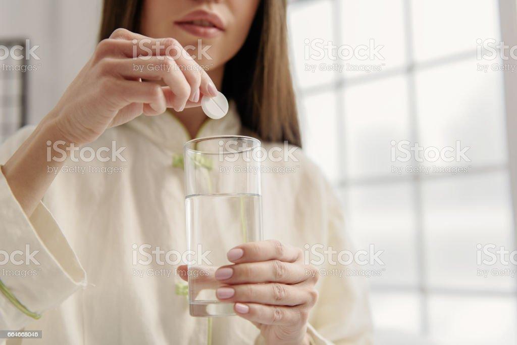 Serene woman adding vitamin liquid stock photo