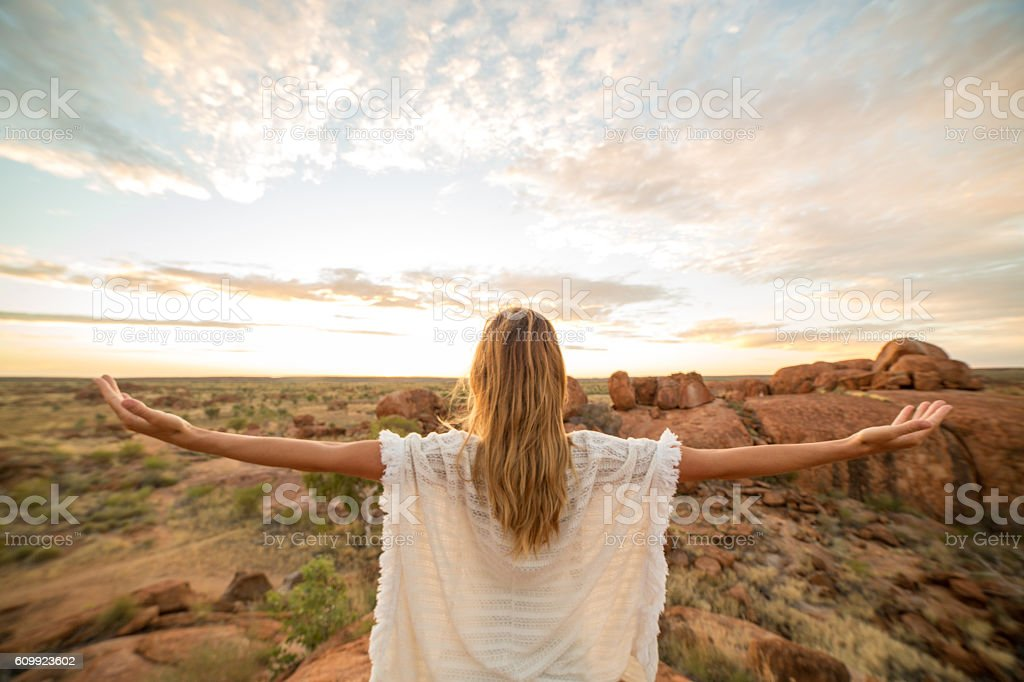 Serene woman arms outstretched in nature, sunrise stock photo
