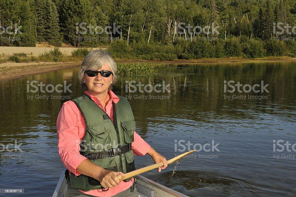 Serene Woman canoeing on mountain lake stock photo