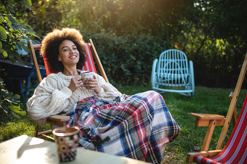 Lovely and serene mixed ethnicity woman enjoying a spring day outdoors in a back yard, sitting on a lounge chair and drinking tea.