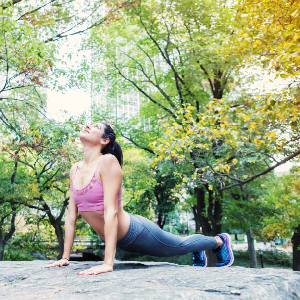 Serene woman holds yoga pose Serene athletic woman holds a yoga pose while exercising in a city park. upward facing dog position stock pictures, royalty-free photos & images