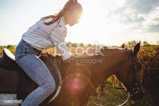 Beautiful woman enjoying horseback riding in nature.