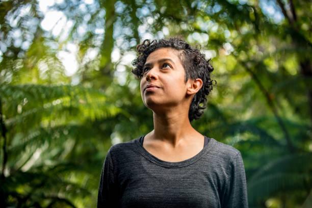 serene woman in lush outdoor setting - ambientalista foto e immagini stock