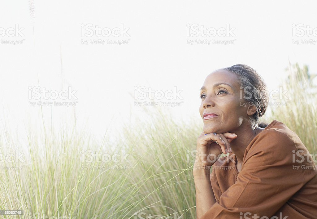 Serene woman sitting in sunny field stock photo