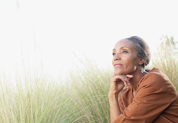 tranquila mujer sentada en el soleado campo - estilo de vida austero fotografías e imágenes de stock