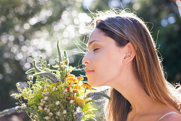 serene woman smelling bouquet - scented stock photos and pictures