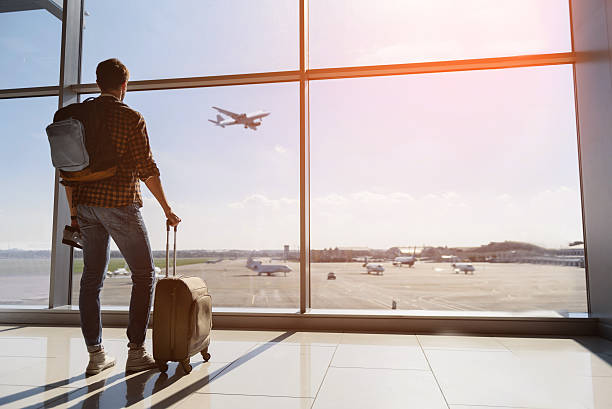 Serene young man watching plane before departure Calm male tourist is standing in airport and looking at aircraft flight through window. He is holding tickets and suitcase. Sunset travel stock pictures, royalty-free photos & images