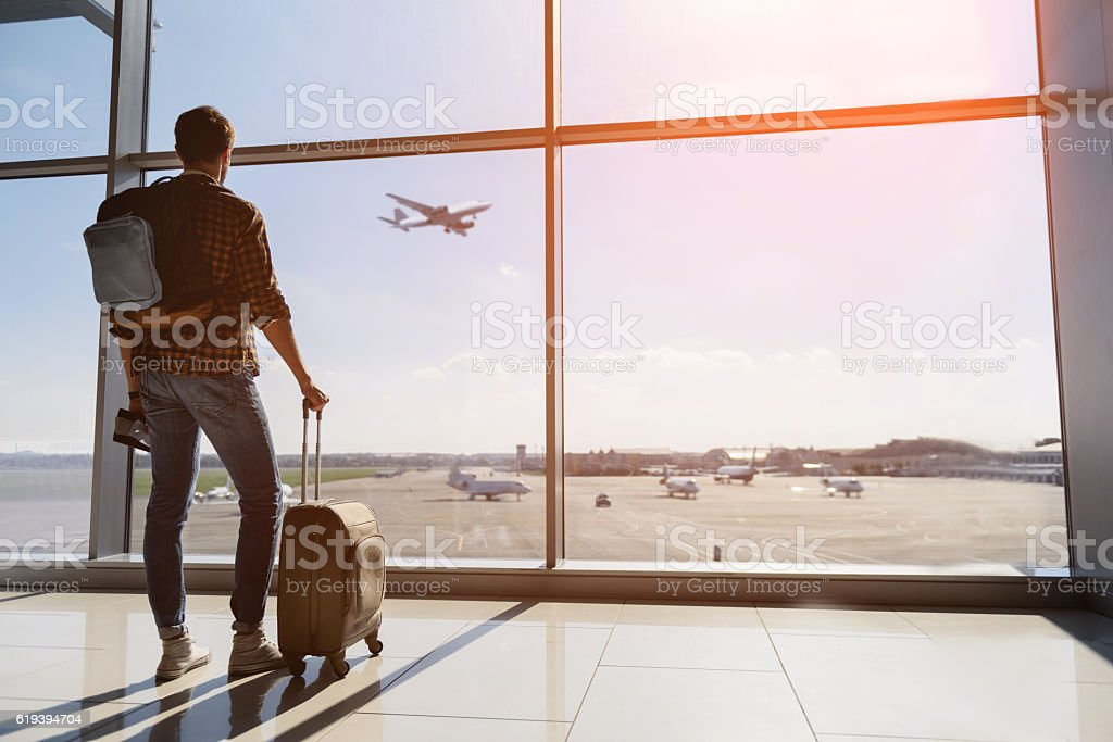 Serene young man watching plane before departure - foto de stock