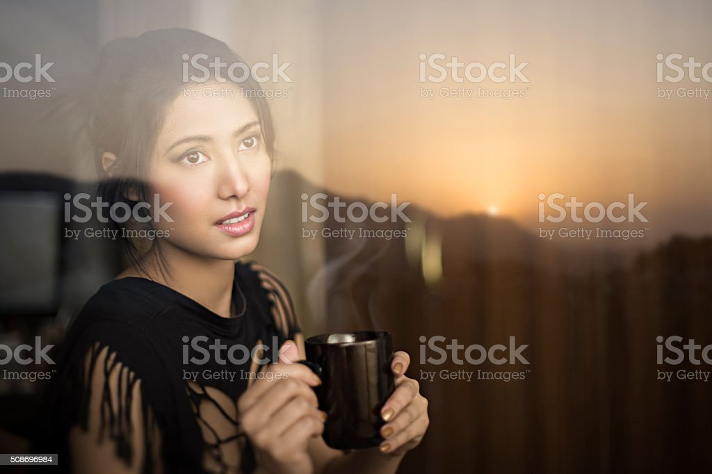 Serene young woman enjoying sunrise view and having coffee break. stock photo