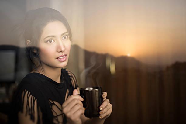 Serene young woman enjoying sunrise view and having coffee break. stock photo