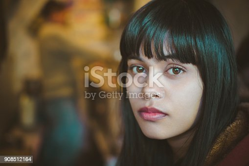 Indoor image of serene Asian, Indian young woman at home. She is sitting in kitchen at day time and looking at camera with blank expression. One person, head shot and selective focus with copy space.