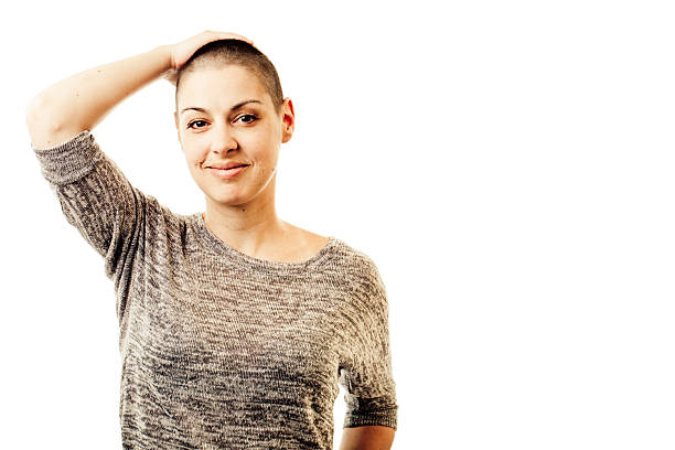 Serene Young Woman Portrait of a beautiful young woman with shaved head, serene, looking at camera. May be use for cancer concepts. shaved head stock pictures, royalty-free photos & images
