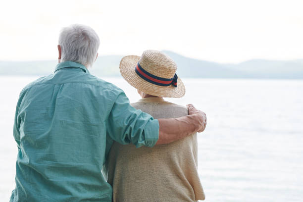 Serenity and peace Peaceful and romantic senior couple in casualwear spending time by seaside and enjoying weather and the day riverbank stock pictures, royalty-free photos & images