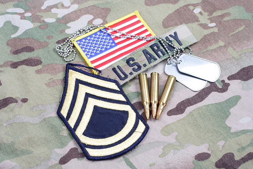 istock US ARMY Sergeant First Class rank patch, flag patch, with dog tag and 5.56 mm rounds on camouflage uniform 1190926103
