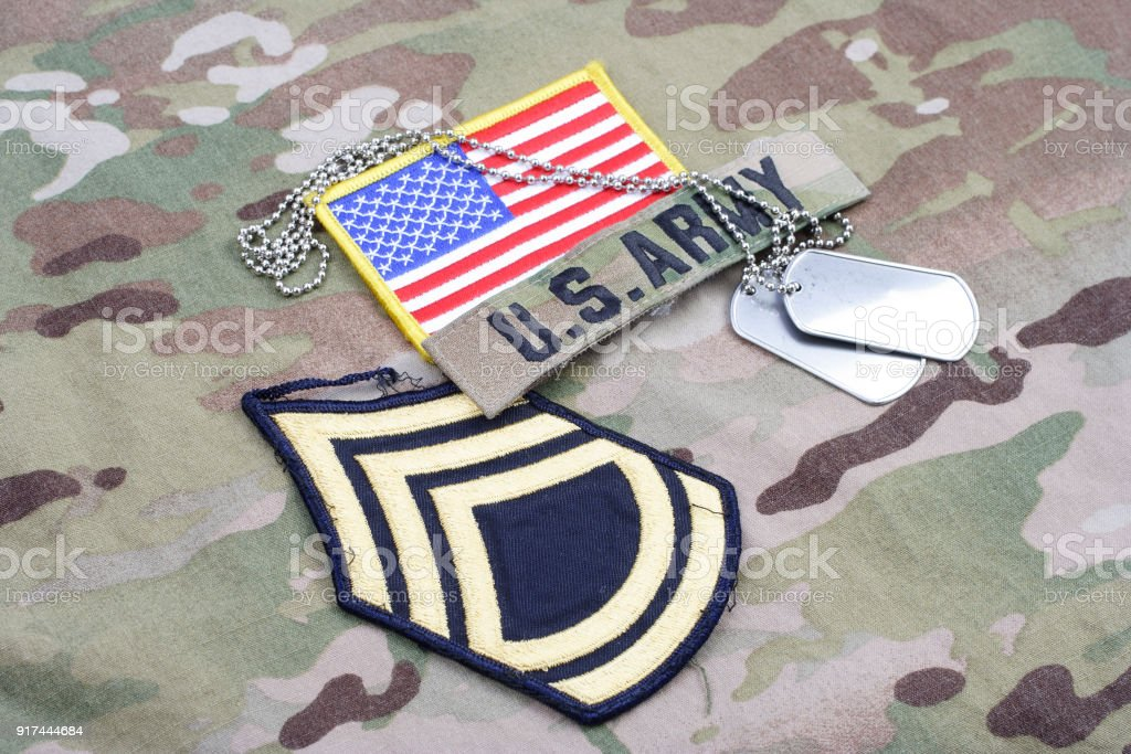 US ARMY Sergeant First Class rank patch, flag patch, with dog tag on camouflage uniform stock photo
