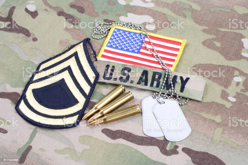 US ARMY Sergeant First Class rank patch, flag patch, with dog tag with 5.56 mm rounds on camouflage uniform stock photo