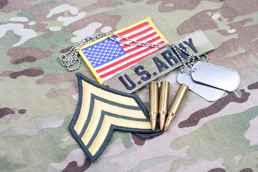 istock US ARMY Sergeant rank patch, flag patch, with dog tag and 5.56 mm rounds on camouflage uniform 1190926134