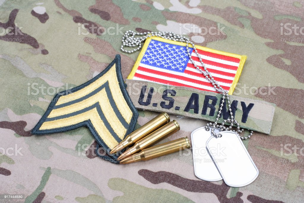 US ARMY Sergeant rank patch, flag patch, with dog tag with 5.56 mm rounds on camouflage uniform stock photo